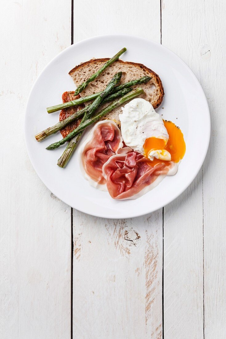 Frühstück mit pochiertem Ei, Parmaschinken und grünem Spargel auf weißem Teller