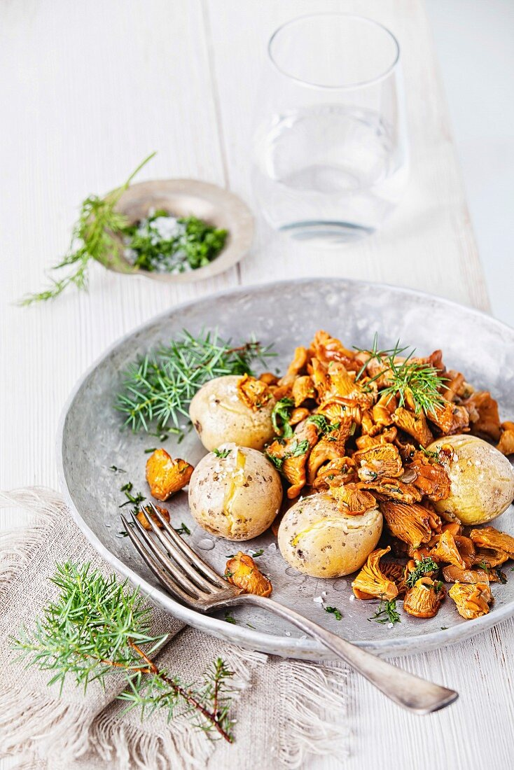 Fried chanterelles with potatoes and onion on white wooden background