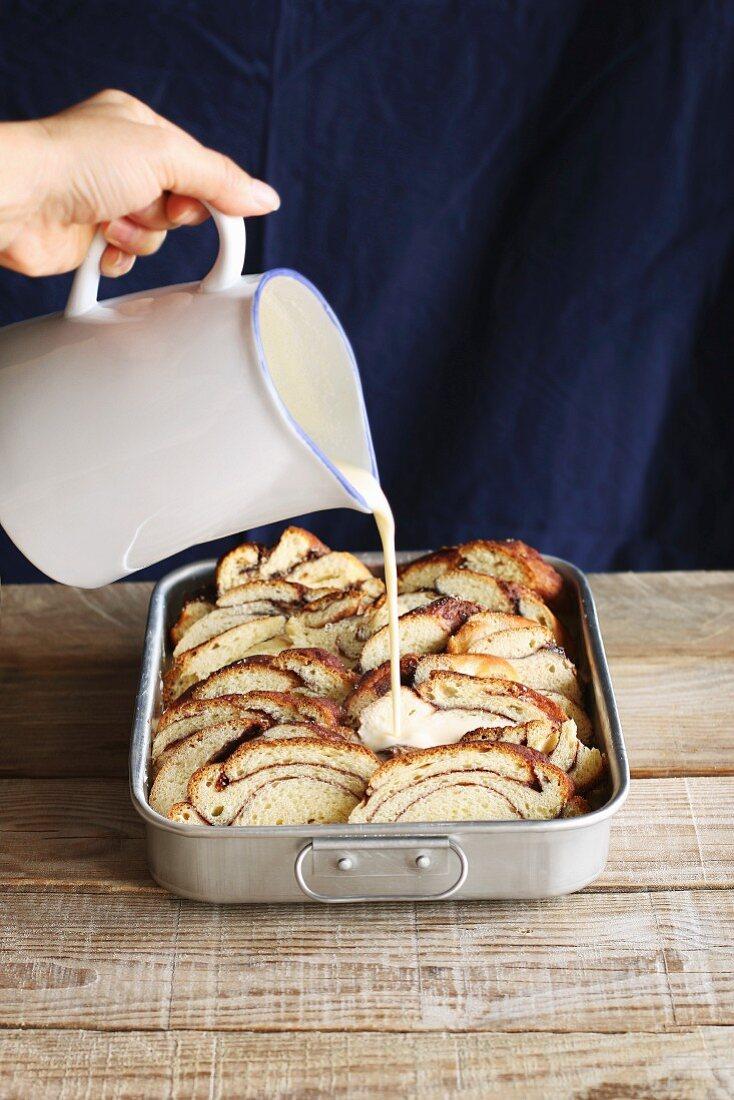 Preparing bread pudding, pouring egg mixture over slices of brioche bread in a pan