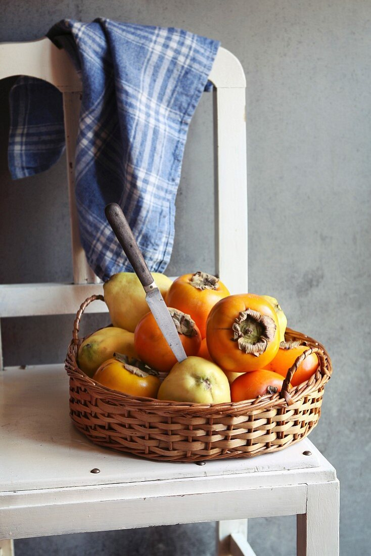 Still life with quince and persimmon on a rattan tray