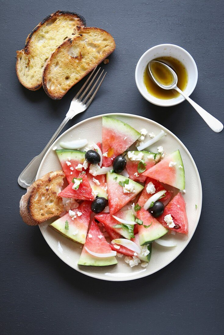 Watermelon salad with feta cheese, black olives, onion and basil