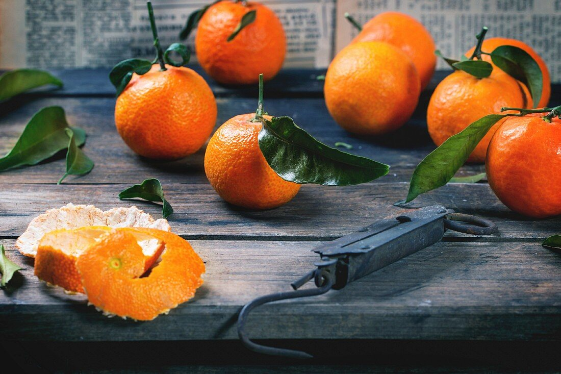 Tangerines with leaves and vintage steelyard on old wooden table
