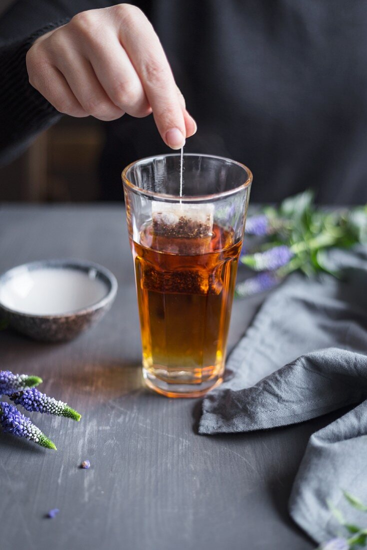 A woman dipping a tea bag into a glass of hot water
