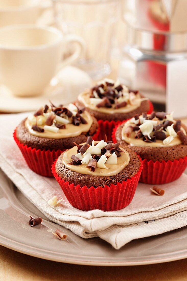 Mocha chestnut cupcakes on a cream napkin and plate with coffee cups and percolator in background