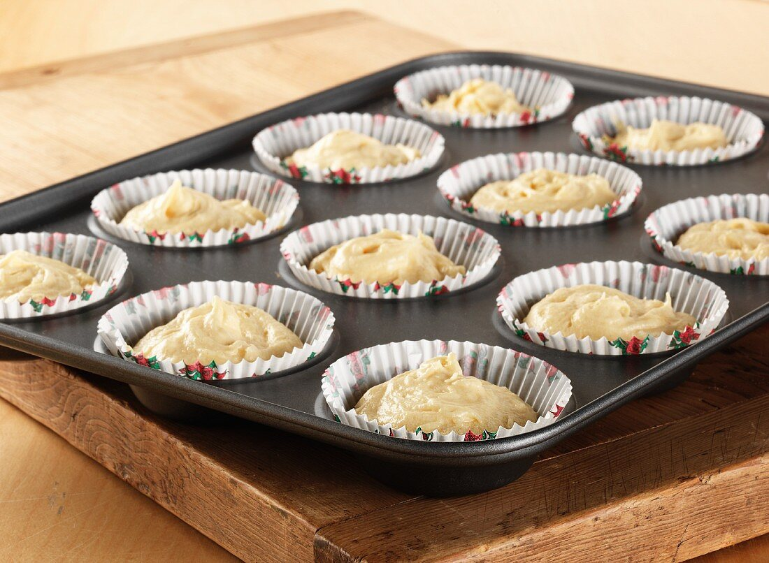 Uncooked cupcake mixture in cupcake cases and a cupcake tin sitting on a wooden board all on a wooden table