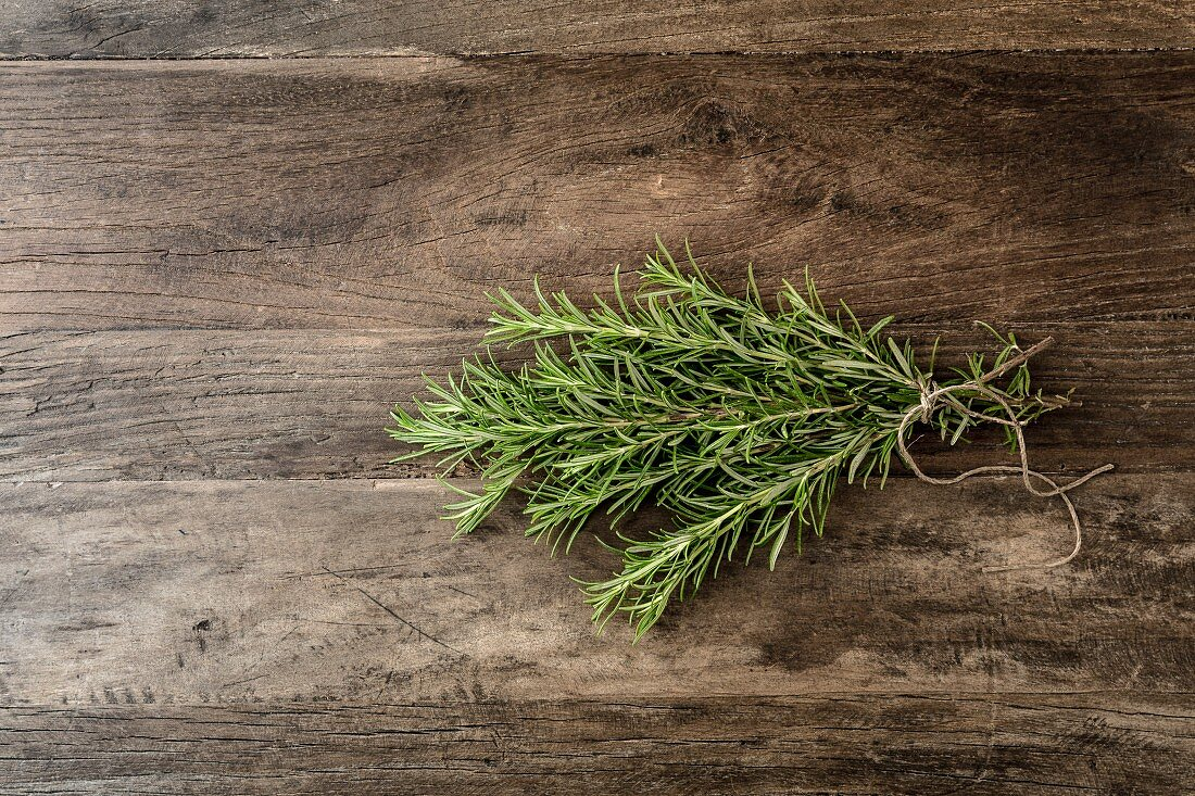 Bunch of rosemary stems tied with string on a wooden surface