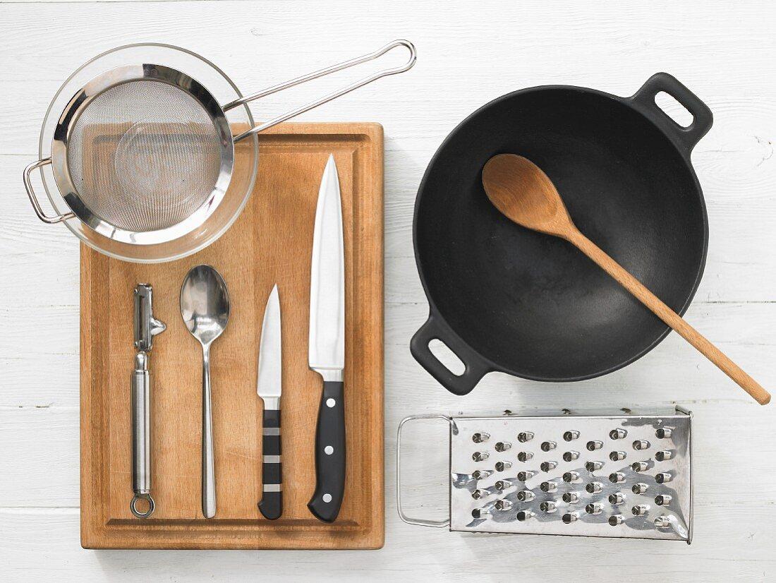Various kitchen utensils: wok, grater, strainer, vegetable peeler, knives