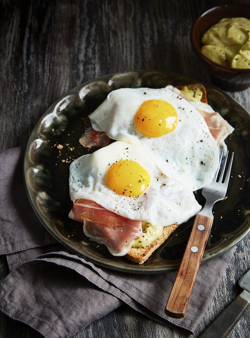 Toasted bread topped with parma ham, two fried eggs and mango guacamole