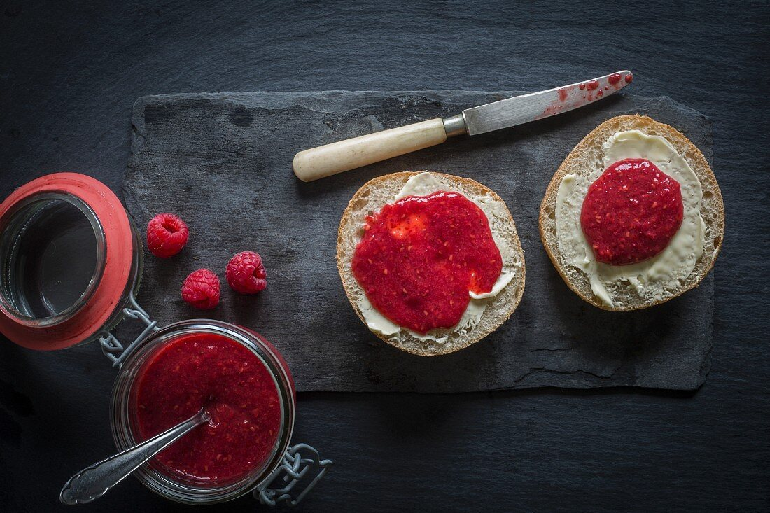Open jar of raw raspberry and chia jam and bread rolls with butter and jam on black slate board