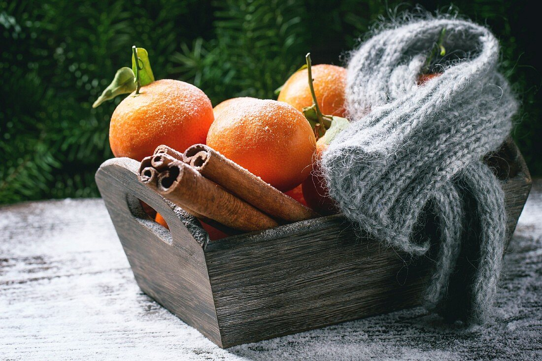 Wooden basket with tangerines, cinnamon sticks and scarf over wooden background with snow and cone