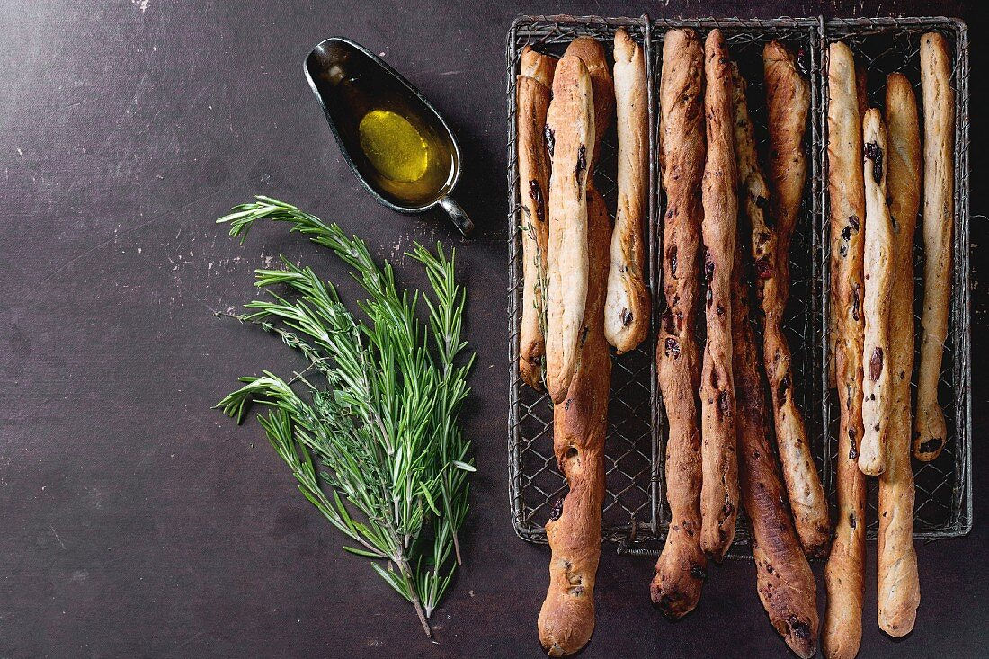 Fresh baked homemade grissini bread sticks in vintage metal grid box with olive oil and herbs rosemary and thym