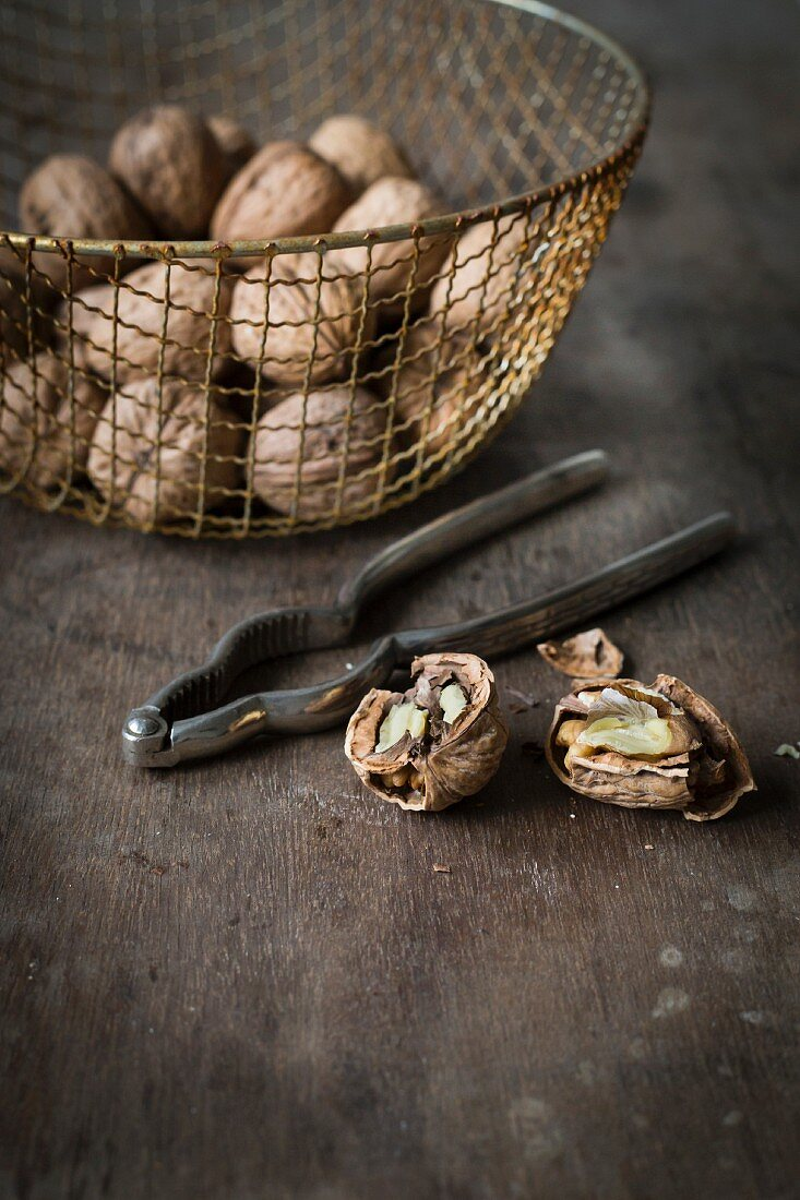Walnuts in vintage wire basket on wooden table