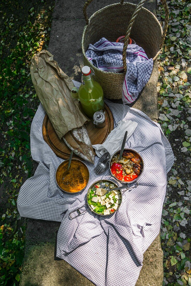 Picnic basket and blanket with artisan bread and vegan dishes