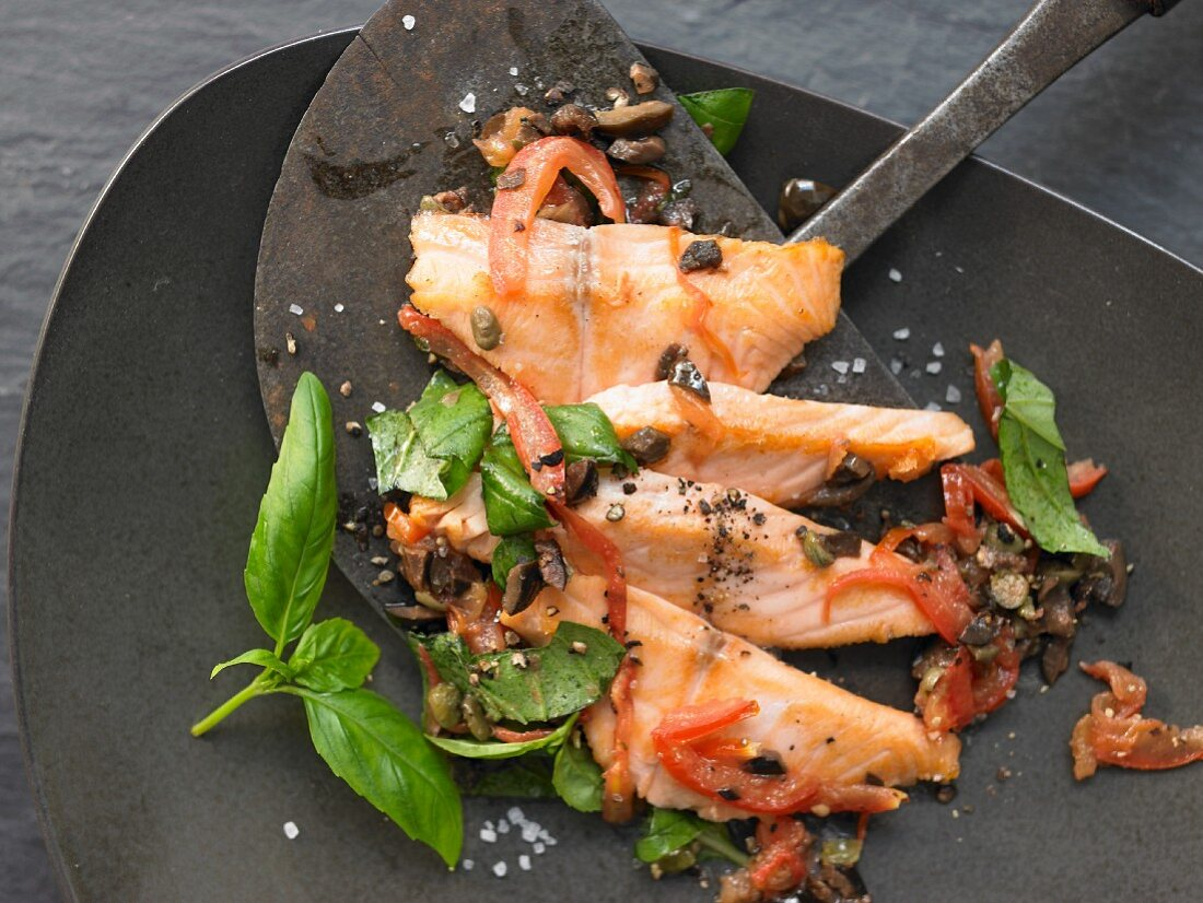 Salmon fillet with tomato, black olives and basil