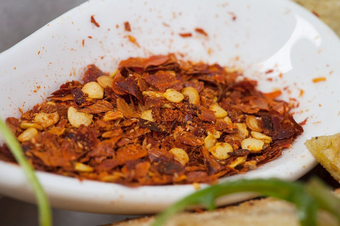 Crushed chillies in a ceramic bowl (close-up)