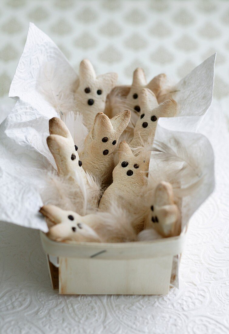 Easter bunny biscuits, white feathers and napkin in chip wood basket