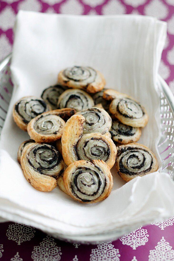 Poppyseed and puff pastry swirls on white linen napkin