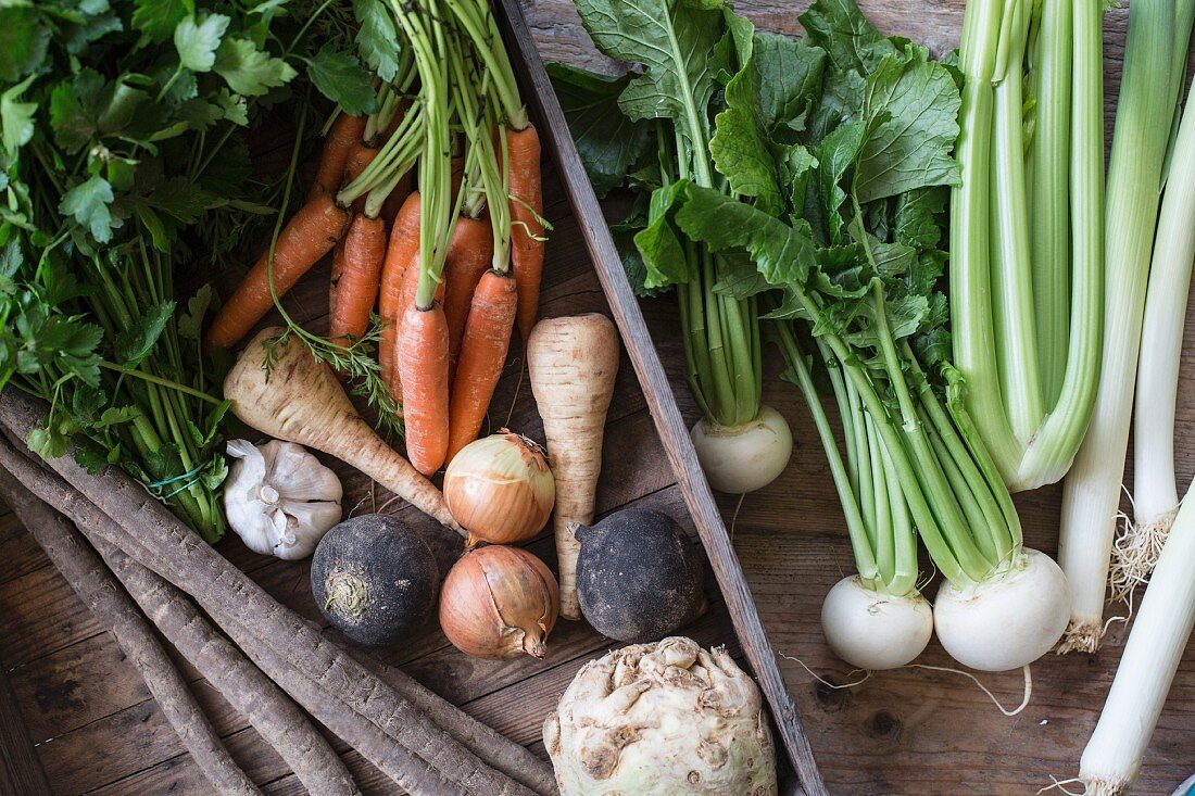 A vegetable crate with root vegetables, onions and parsley