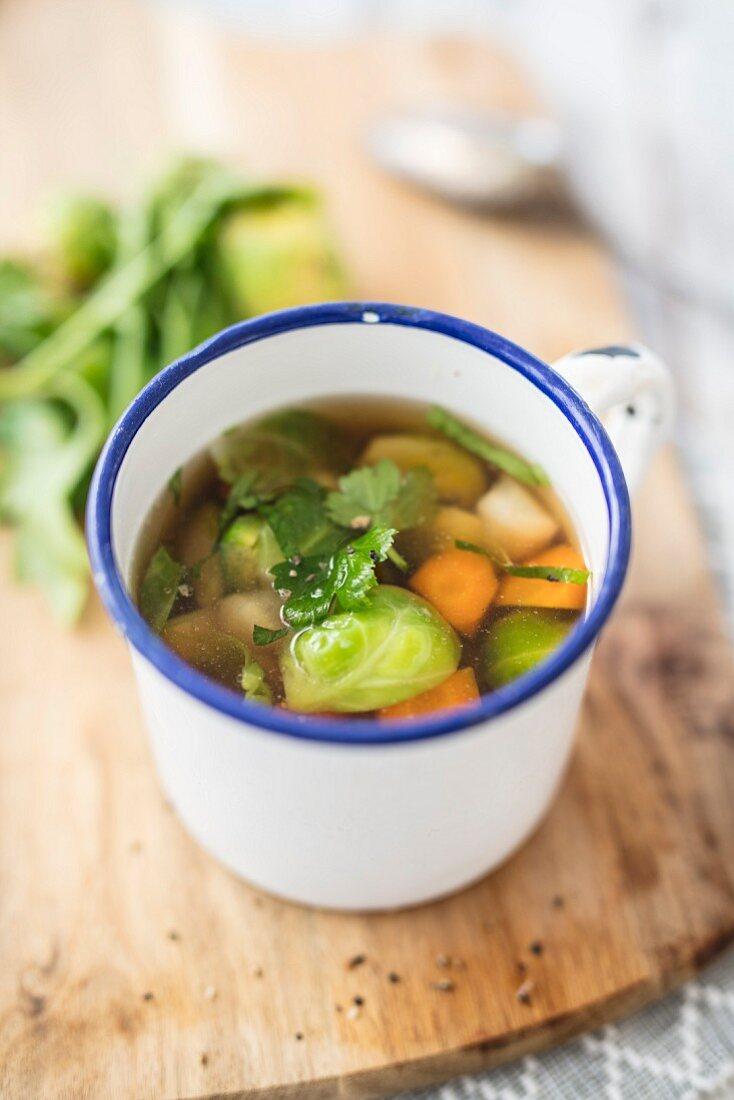 Vegetable broth in an enamel cup
