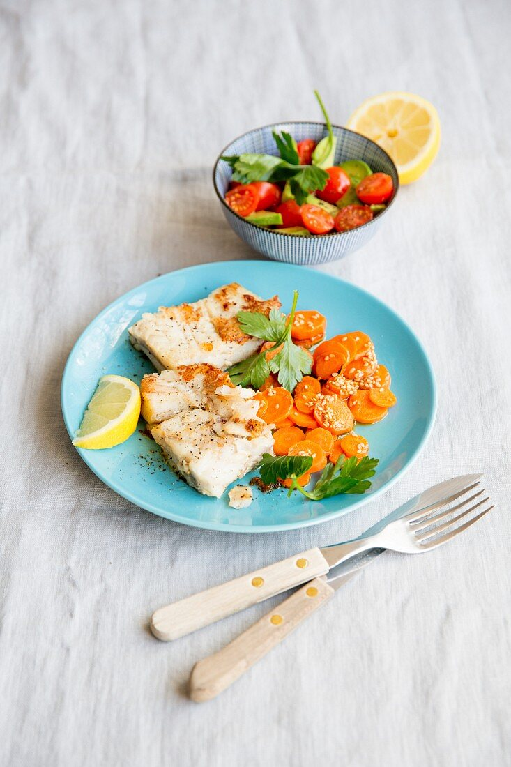 Salmon fillet with carrots and a tomato and avocado salad