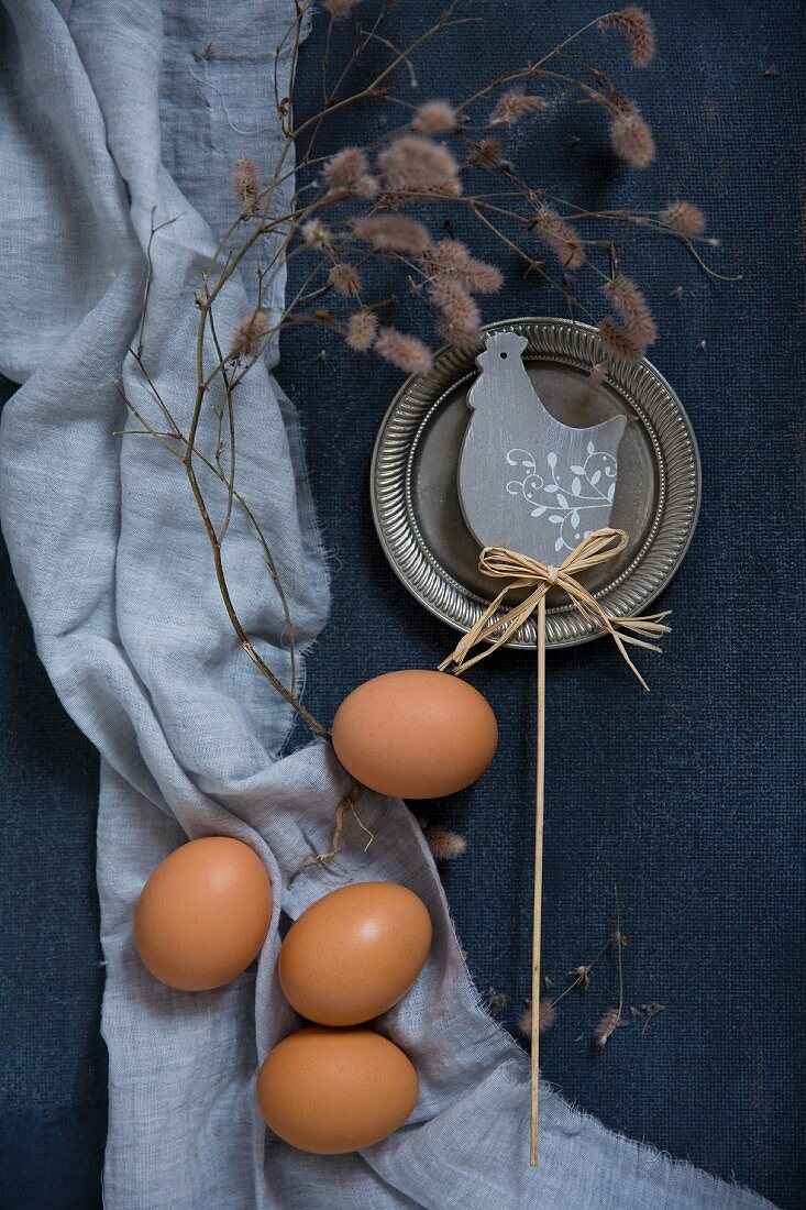 Easter decorations with chicken eggs and a branch beside a chicken motif on a blue background