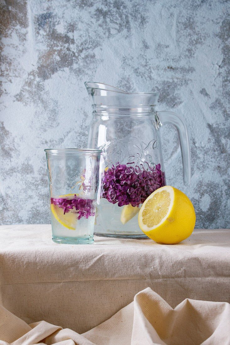 Glass and pitcher of lilac lemonade water with lemon and lilac flowers
