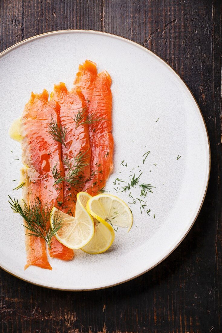 Smoked Salmon with dill and lemon on white plate
