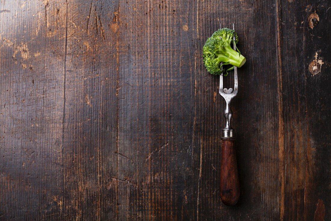 Fresh broccoli on meat fork on dark wooden background