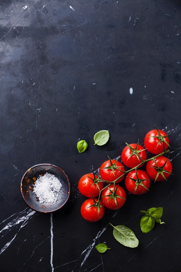 Cherry tomatoes and green basil leaves on dark marble background