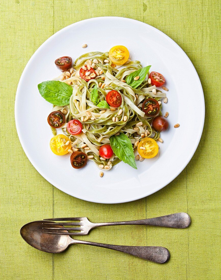 Spaghetti with tomato and basil on green background