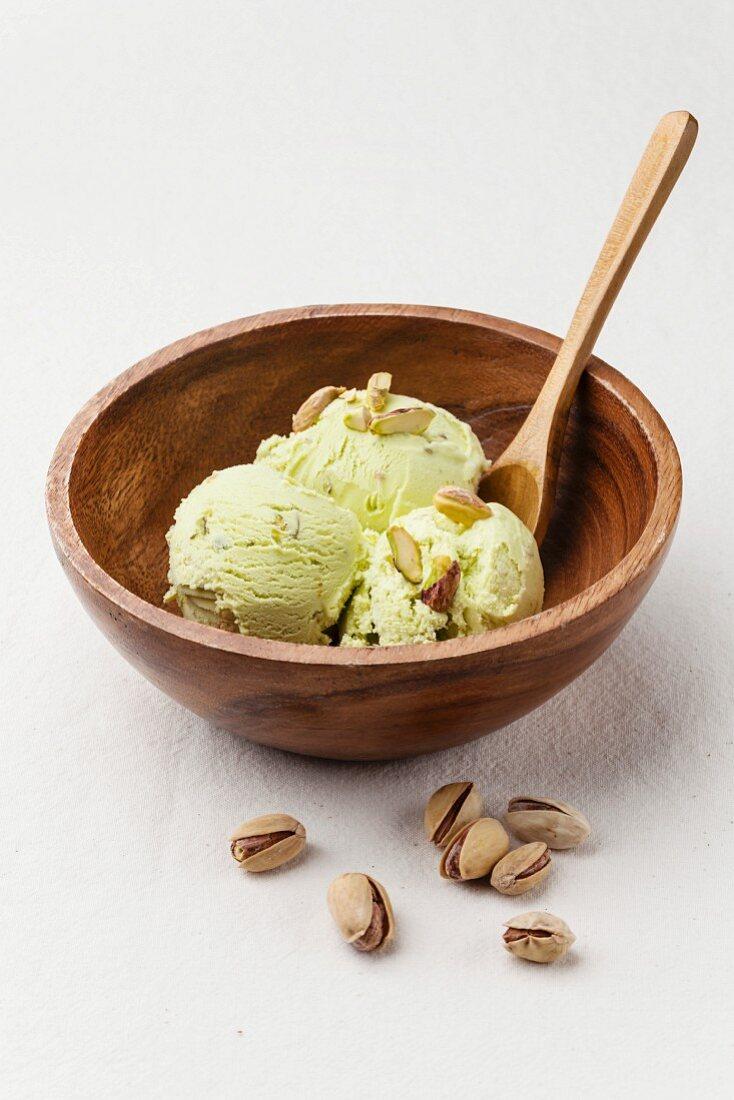 Pistachio ice cream in wooden bowl