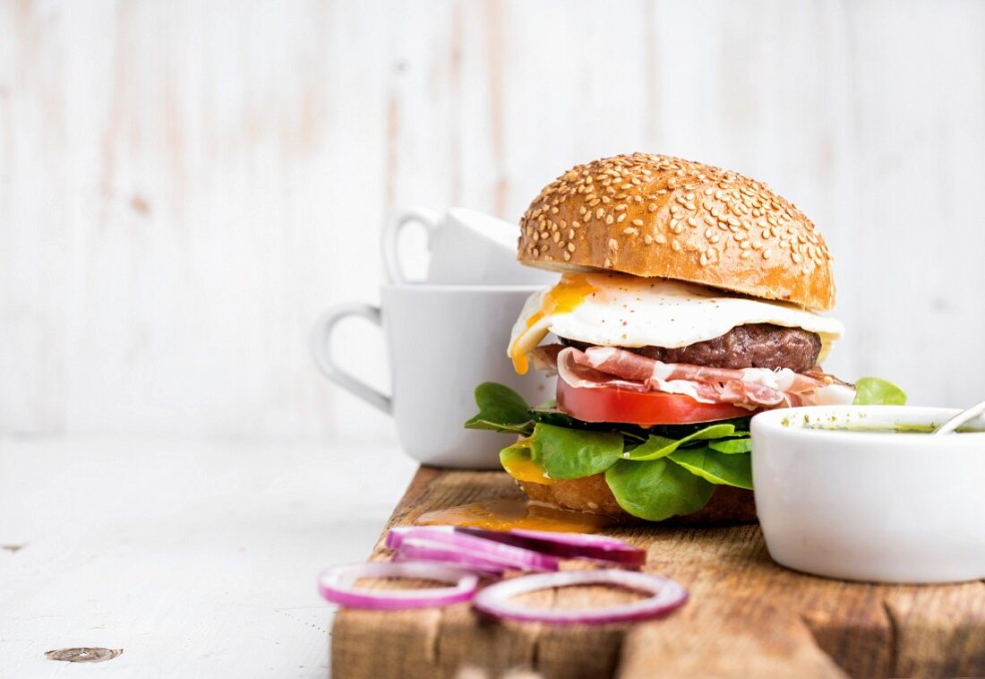 Homemade beef burger with fried egg and vegetables, onion rings and coffee cups on wooden board
