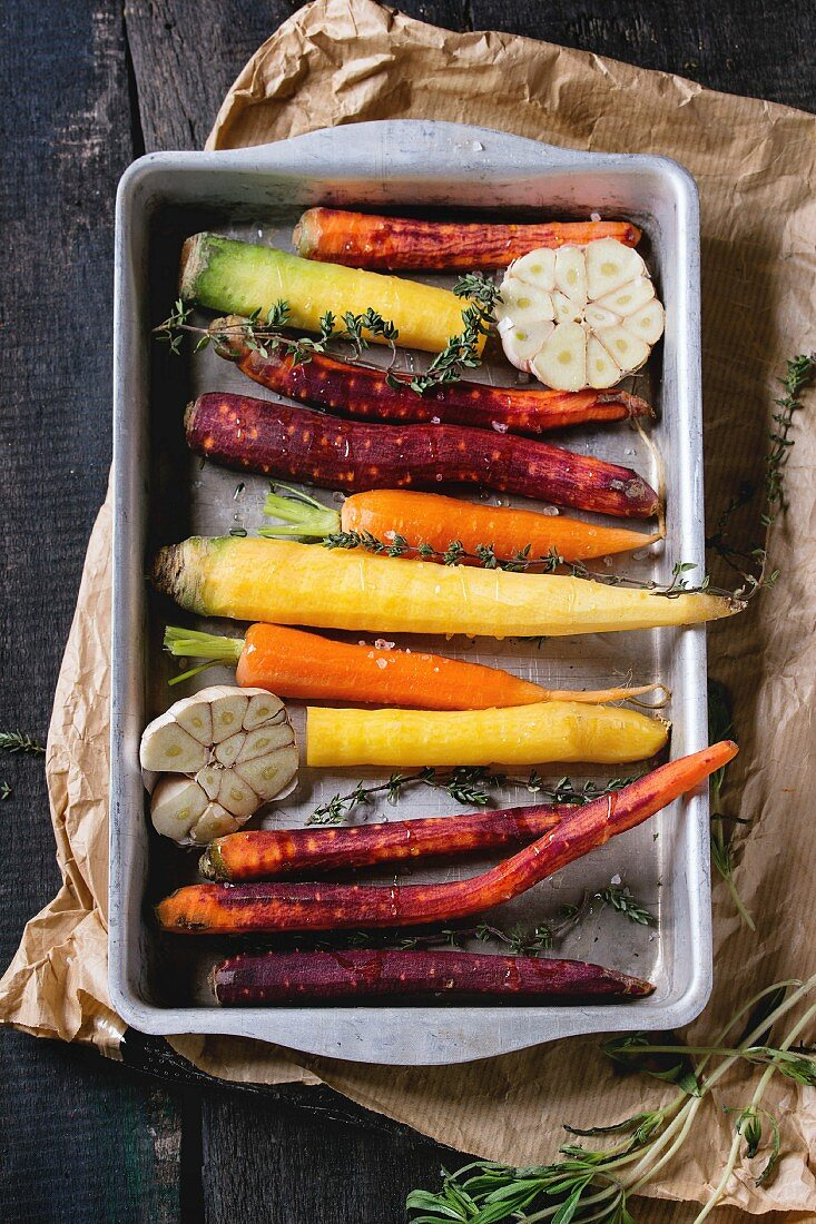 Ready for baking peeled colorful raw carrots with fresh thyme herbs and sliced garlic in aluminum tray