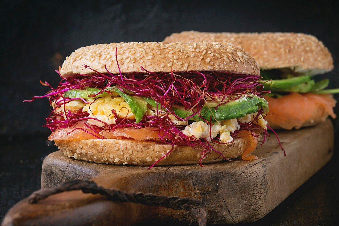 Two Bagels with salted salmon, spinach, beetroot sprouts, avocado and scrambled egg on wooden chopping board