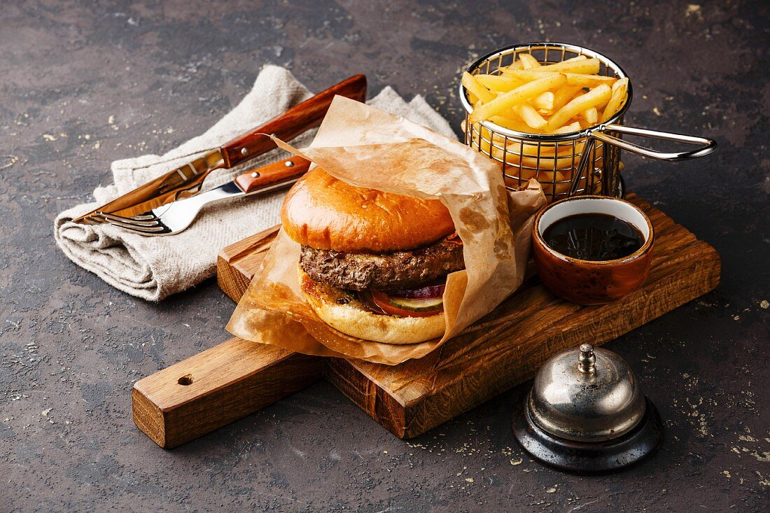 Burger with meat and French fries in basket on dark background and desk bell