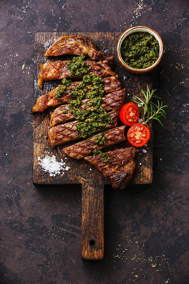 Sliced medium rare grilled beef barbecue Sirloin steak with chimichurri sauce on cutting board