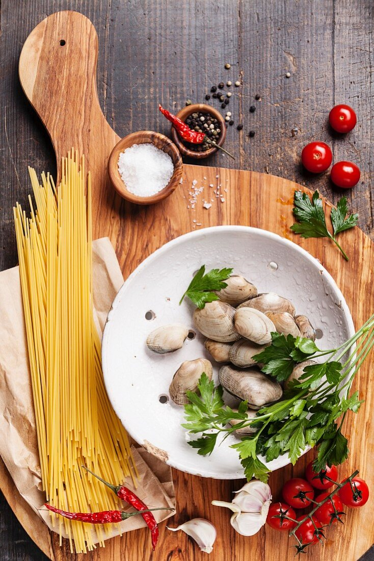 Ingredients for cooking spaghetti vongole Shells vongole, raw sapaghetti, parsley leaves, cherry tomatoes