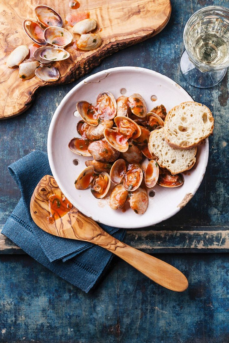 Shells vongole with parsley and tomato sauce in vintage ceramic colander on blue background
