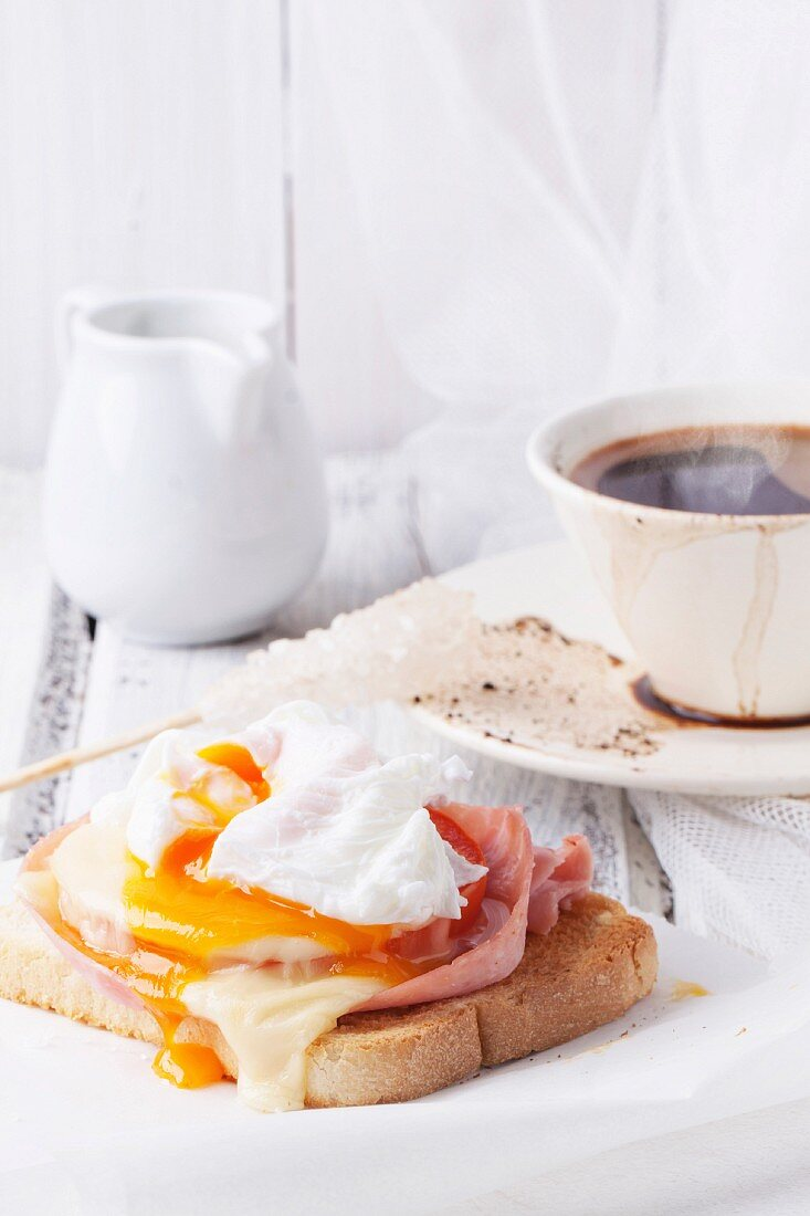 Breakfast with cup of coffee and toast with cheese and poached egg served on white wooden table