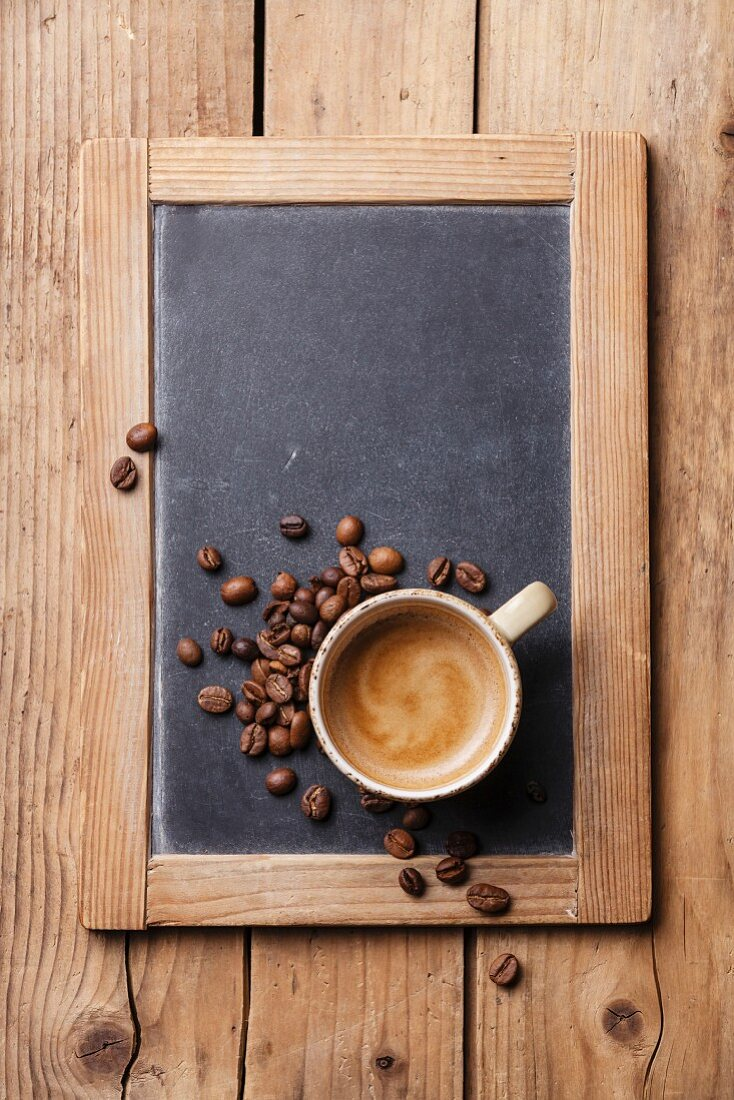 Kaffeetasse mit Kaffeebohnen auf Vintage-Schieferkreidetafel