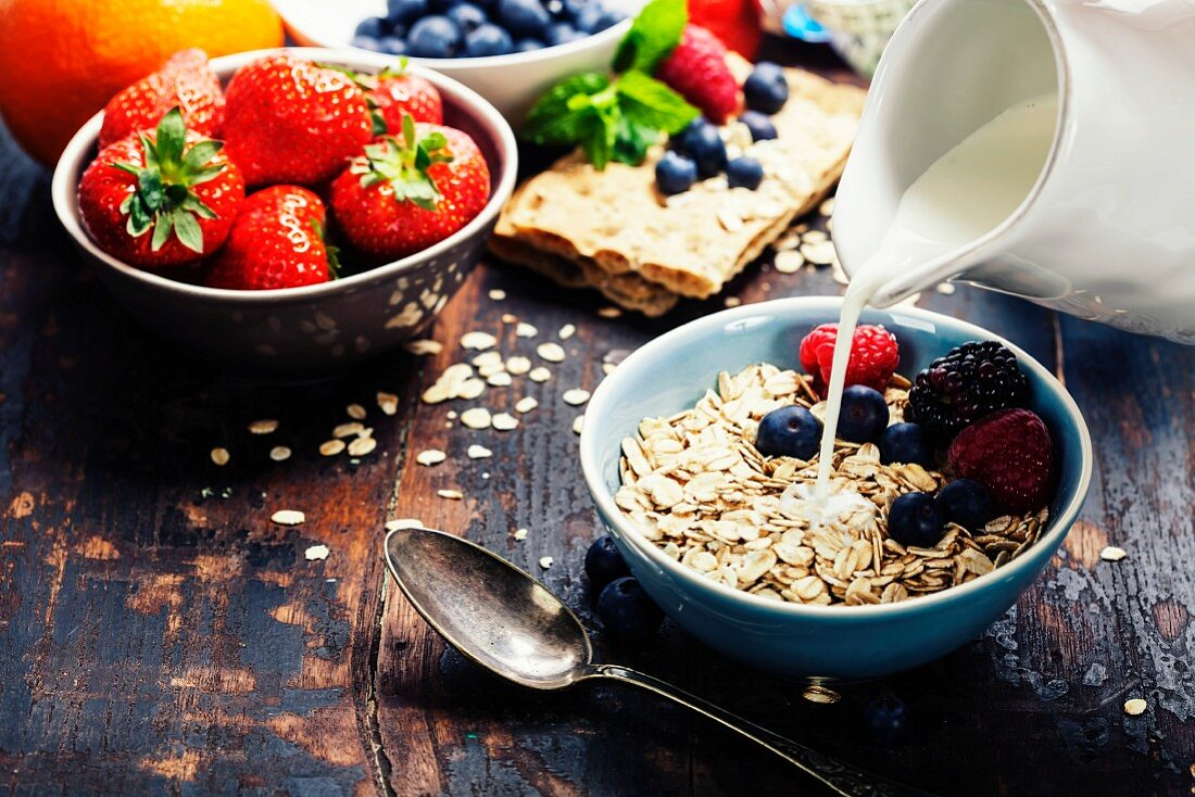Diet breakfast: Bowls of oat flake, berries and fresh milk on wooden background