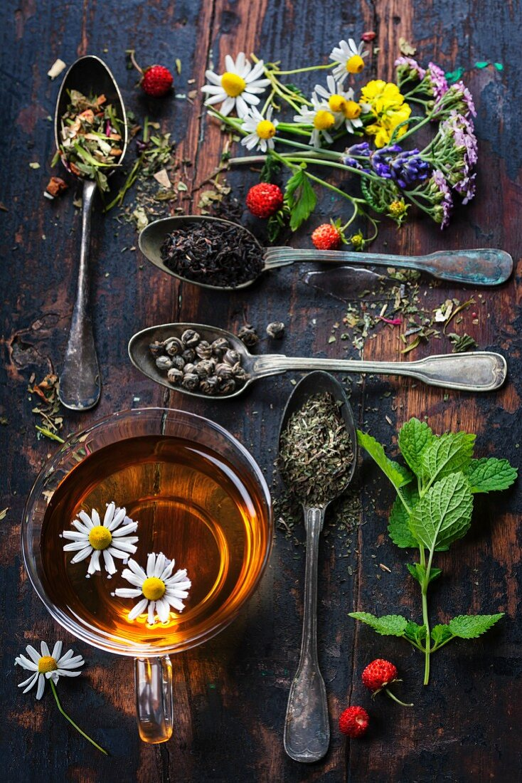 Various kinds of tea with honey, wild berry and flowers on wooden background