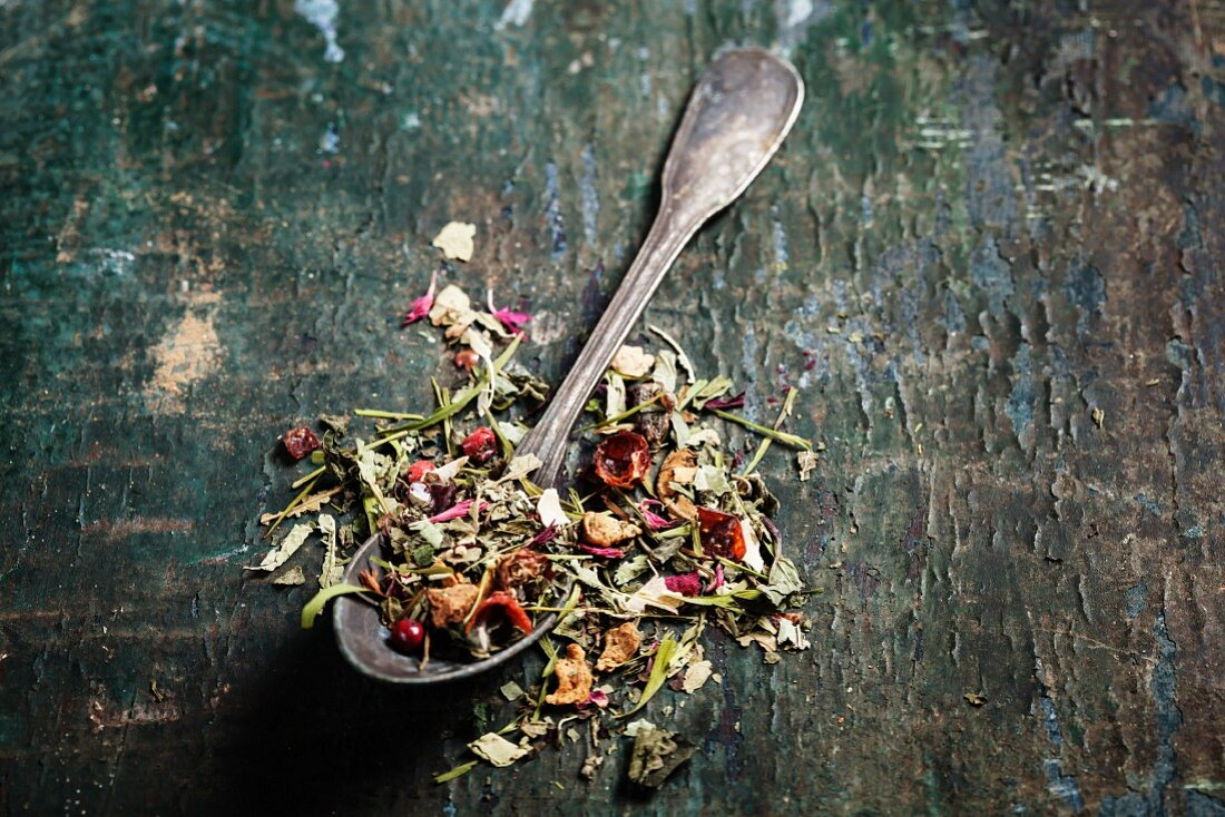 Herbal tea with wild flowers and berry on wooden background