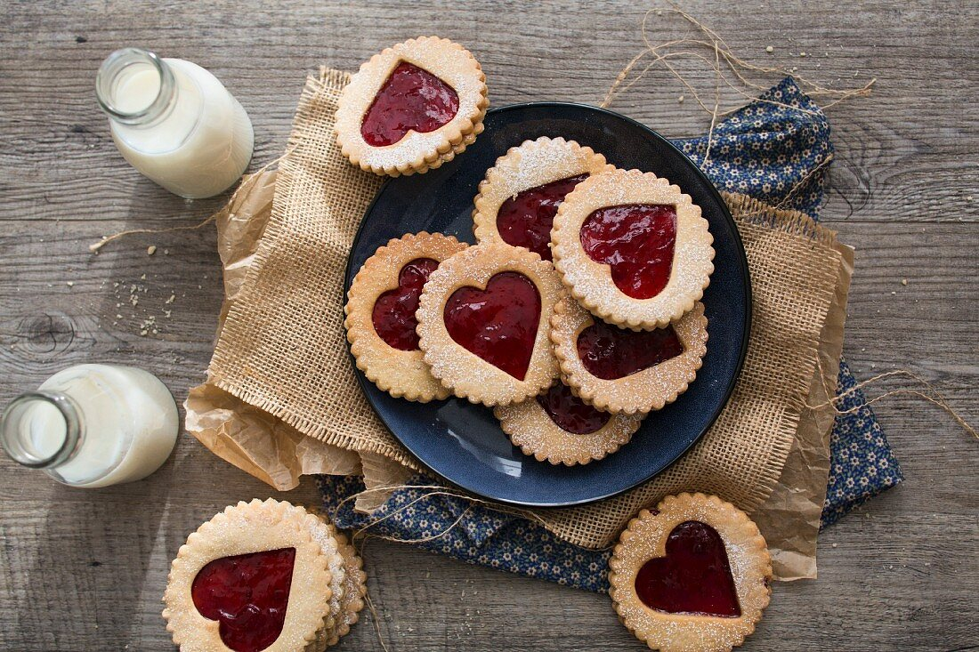Strawberry Jam, heart shaped Linzer Biscuits on a plate with milk bottles
