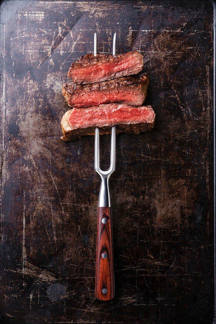 Slices of Rare beef steak on meat fork on dark background