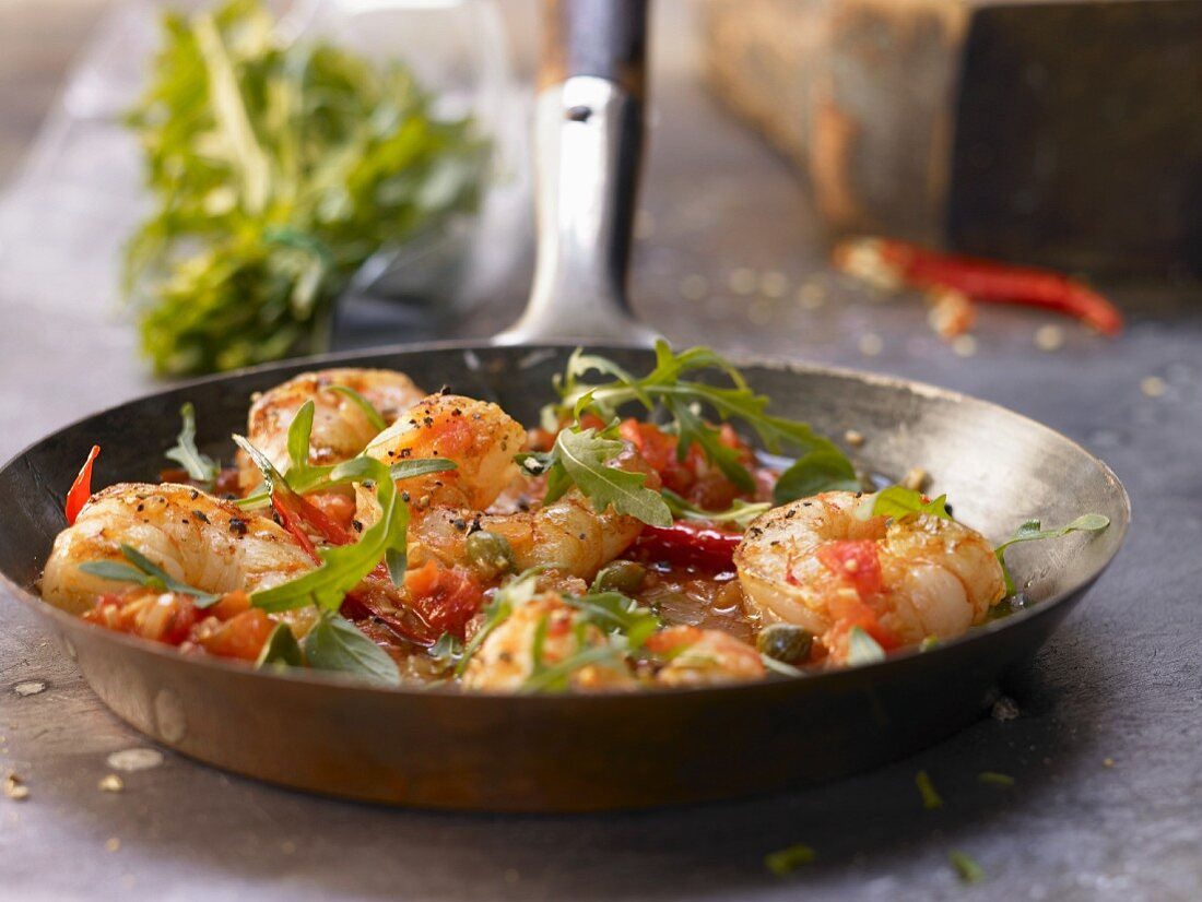 Mediterranean shrimp dish with chilli, tomatoes, capers and rocket