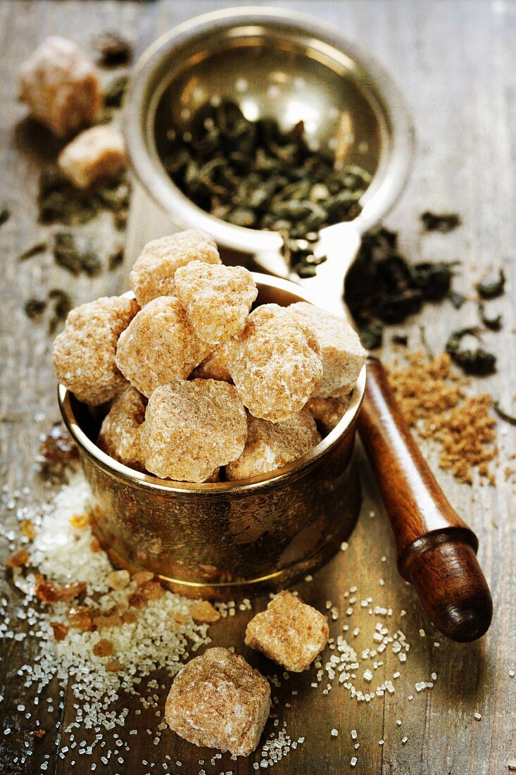 Brown sugar and strainer with tea leafs