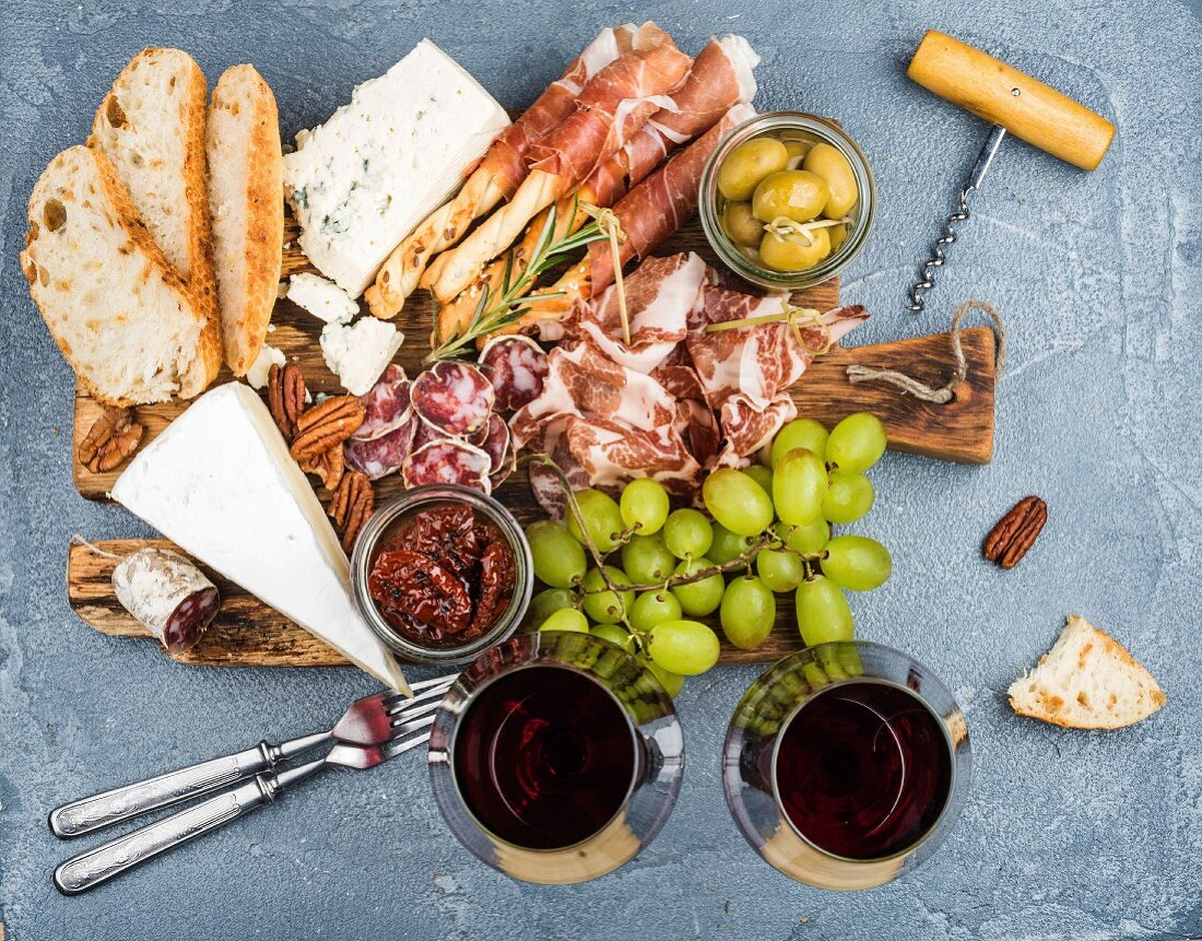 Prosciutto di Parma, salami, bread sticks, baguette slices, olives, sun-dried tomatoes, grapes