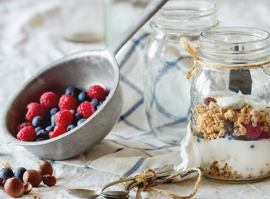 Glass jar with homemade granola and yogurt served with nuts, raspberries and blackberries in vintage colander