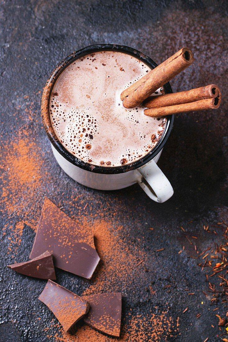 Vintage mug of hot chocolate with cinnamon sticks over dark background
